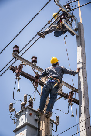 essentially: Electrician looking at coworker while working on the electricity pole
