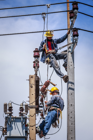 essentially: Electricians working together on the electricity pole