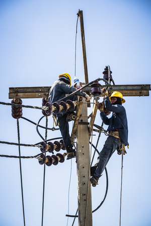 essentially: Electrician working together on the electricity pole