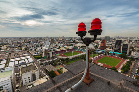 twin red obstruction lights on the rooftop with city view in the background Stock Photo