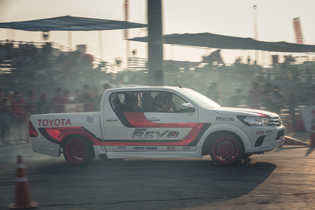 October 18, 2015: Toyota Hilux Revo perform drifting contest on the track between driver from Thailand and Japan at the event Toyota Motor Sport show at Udon Thani, Thailand with motion blur of the background and smoke of the burning tires