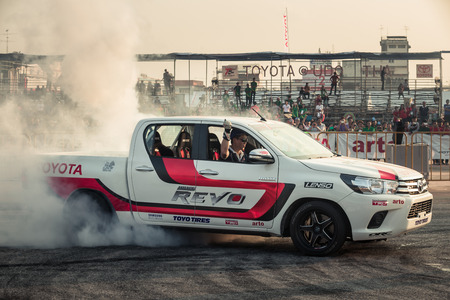 October 18, 2015: Techapol Toyingchareon the driver of Toyota Hilux Revo perform drifting contest on the track between driver from Thailand and Japan at the event Toyota Motor Sport show at Udon Thani, Thailand with  smoke of the burnout tires