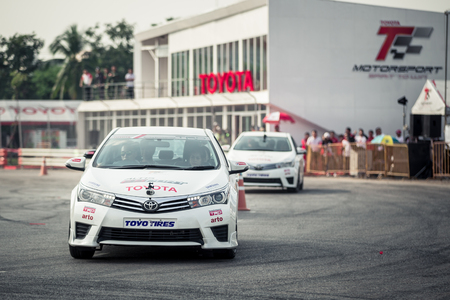 drifting: October 18, 2015: Toyota Colora Altis perform drifting on the track at the event Toyota Motor Sport show at Udon Thani, Thailand with people looking in the background