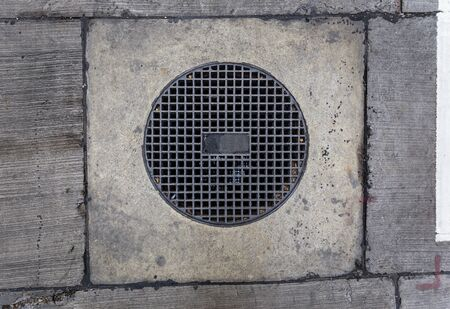 round sewer with holes and rectangular frame of the cement on it