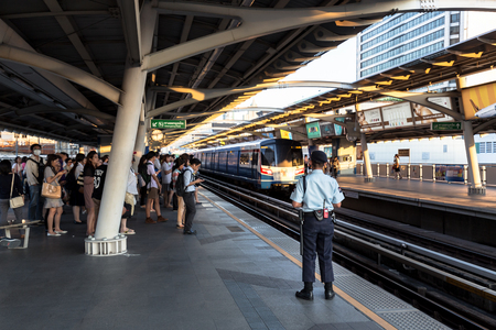 they are watching: Bangkok, Thailand - January 18, 2016 : Security guard watching people while they waiting for the train to come to ensure safety of the passengers at BTS National Stadium station in the rush hour. Daily passengers of BTS skytrain is around 700,000