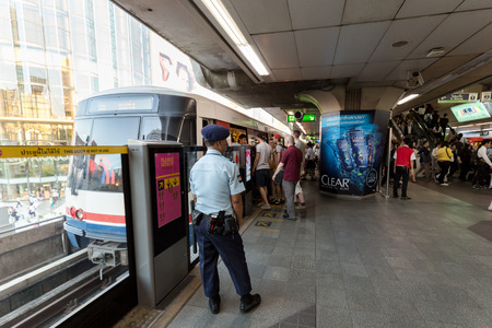 go inside: Security guard watching people to go inside the train safely at BTS Siam station in the rush hour. Daily passengers of BTS skytrain is around 700,000 Editorial