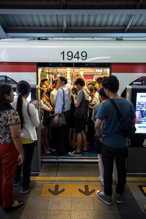 go inside: BTS skytrain full of people in the train and people waiting to go inside the train in the waiting zone at BTS Siam staion in the evening. Daily passengers of BTS skytrain is around 700,000