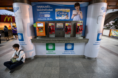chit: public payphone and top up machine on the corner with advertisement poster in Thai language in the background at BTS Mo Chit station in the evening with unidentified man sitting in the corner. Editorial