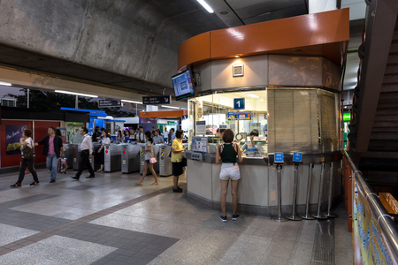 chit: Ticket office at the BTS Mo Chit station at the evening with 2 people buying a ticket and a lot of people walking out from the inside of the station. Daily passengers of BTS skytrain is around 700,000. Editorial