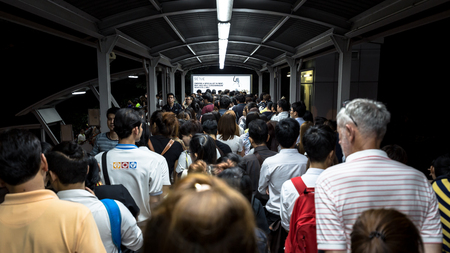 chit: Crowd of people walking out from the BTS Mo Chit station to the road in the rush hour at night. They have to walk cross a footbridge along with lights and advertising board. Daily passengers of BTS skytrain is around 700,000.