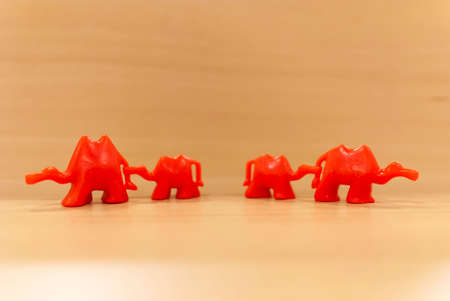 Red toy male and female camels separating and taking a child each. Camera focus on parents. Abstract divorce or sibling separation concept. Ideal for banners Foto de archivo