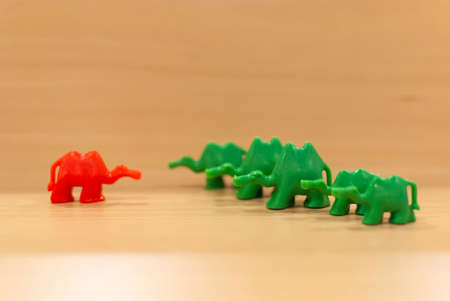One red toy camel standing in front of and against a row of green camels. Uniqueness concept. Ideal for banners.