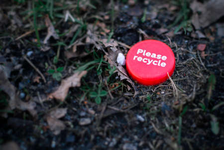 Red bottle cap with Please recycle message lying ironically on the grass ground in the middle of a park. Recycling concept.