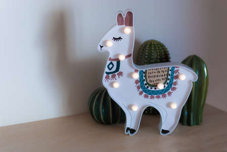 A trendy llama kids night lamp standing on a bedside in dawn or sunrise light with ceramic cactuses behind it.