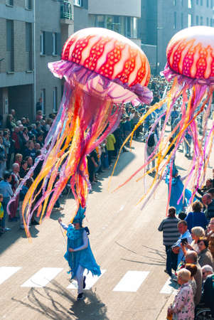 Genk, Belgium - May 1st 2019: Participants of annual O-parade. Young women are steering giant floating jellyfishes.