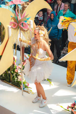 Genk, Belgium - May 1st 2019: Participants of annual O-parade in bright disco outfit with pearls and golden feathers are dancing on their float and waving to crowd Editorial