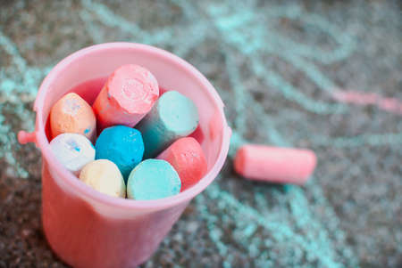 A bucket of colourful chalks against pavement full of scribbles. Toddler or child activity. Back to school
