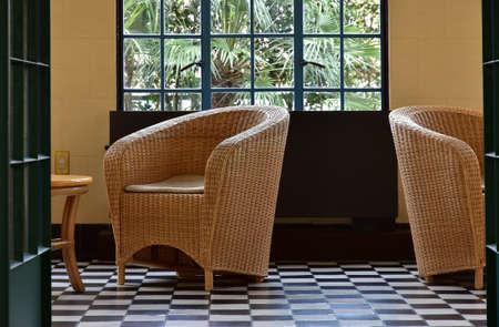 部屋の籐の椅子と窓を風景します。 写真素材
