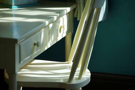 太陽の光が部屋の机と椅子を照らす