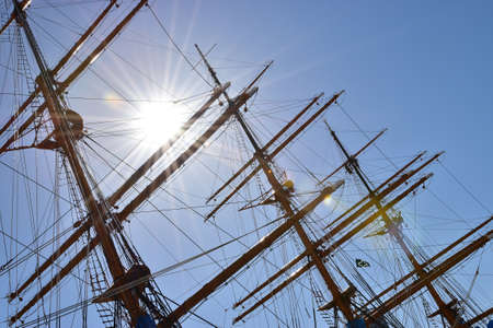 Masts of sailing ships anchored at the port and clear blue sky