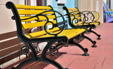 A sight of a yellow bench in a sunny park Stok Fotoğraf