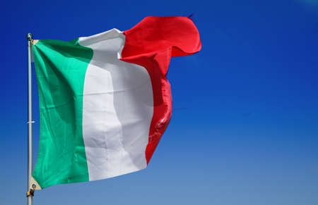 Italian flag fluttering in the blue sky and wind 写真素材