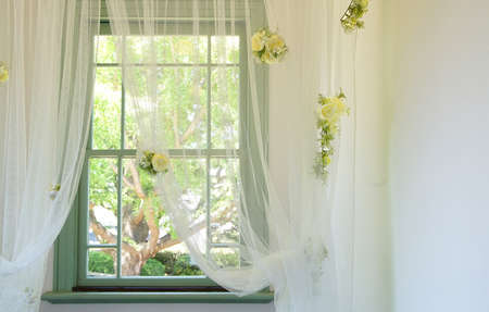 The yellow rose displayed to a window and the curtain of the room 写真素材