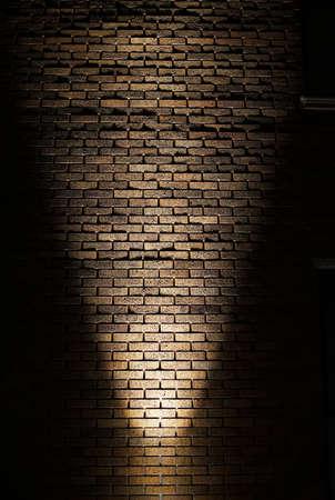 Light shining on brick wall at night 写真素材