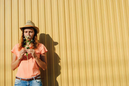 young woman in a cowboy hat smelling a bouquet of chamomile