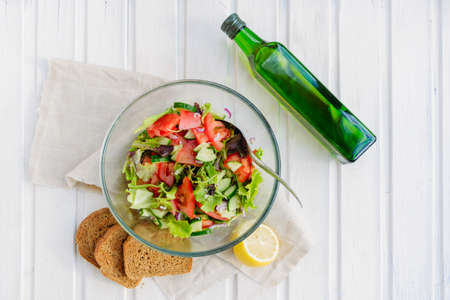 taste of vegetarian summer concept, salad of lettuce leaf, tomato, cucumber, onion, oregano with olive oil and lemon juice on white wooden background with copyspace
