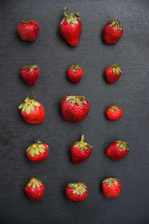 abreast: Strawberries series put on black slate background Stock Photo