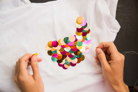 decorates: girl decorates white T-shirt with colored sequins for gift