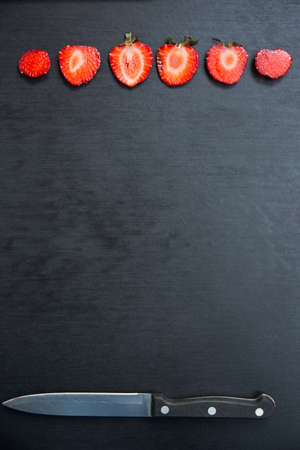 abreast: sliced strawberries and knife on black background with copyspace