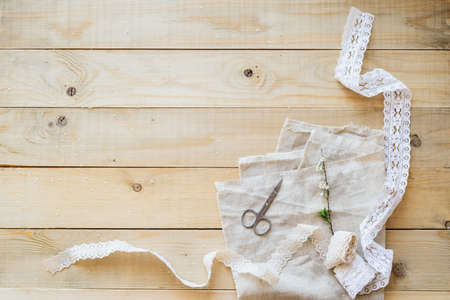flatly: crafts concept, lace ribbon and flowering branch on wooden table Stock Photo