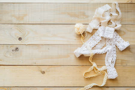 flatly: crafts concept, lace ribbon on wooden background Stock Photo