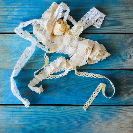 flatly: lace ribbon on wooden background, crafts concept Stock Photo