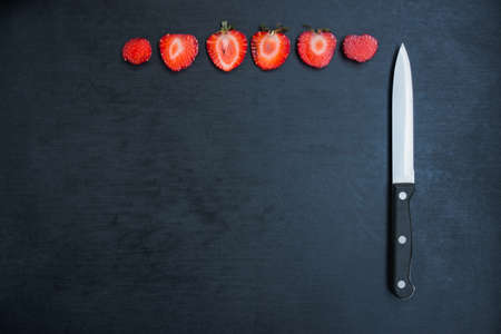 flatly: sliced strawberries and knife on black background with copyspace
