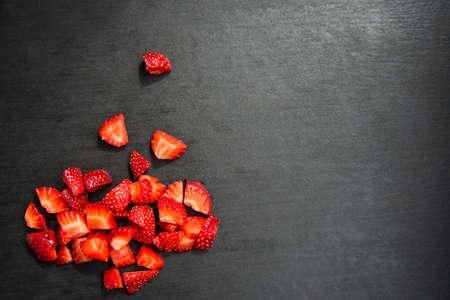 lobule: lobule sliced strawberries on black slate background Stock Photo