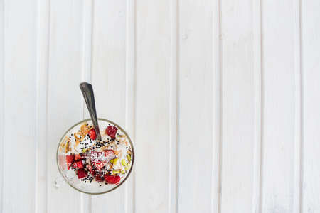 flatly: top view icecream in a cup with strawberry, pistachio, coconut