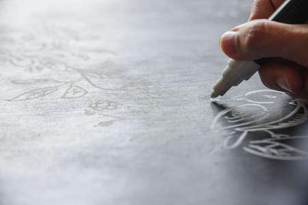 board marker: woman draws chalk marker autumn pattern on a black board Stock Photo