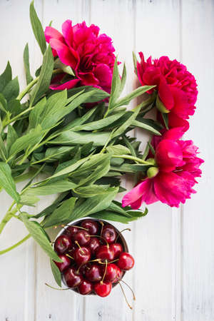 flatly: cherries in bowl with bouquet peonies on white background Stock Photo