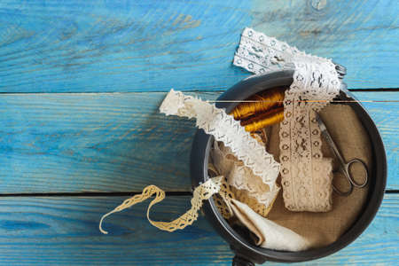 flatly: lace ribbon and scissors in bowl on wooden background Stock Photo