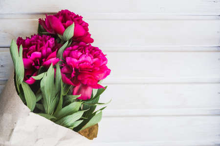flatly: bouquet of peonies on white wooden background Stock Photo