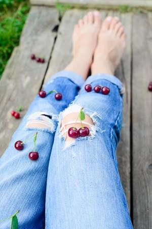 rustic harvester woman legs and fresh ripe cherries Stock Photo