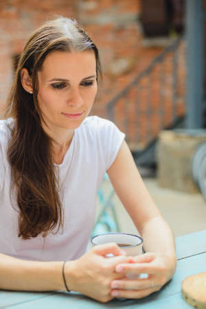 portrait of the brunette girl in outdoor cafe
