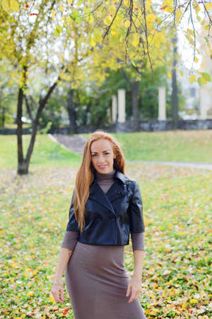 haired young woman posing in the autumn park