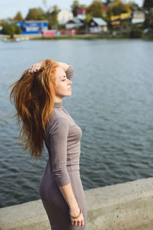 redhead young woman posing in the autumn park near water
