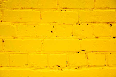 painted yellow brick wall as a background Stock Photo