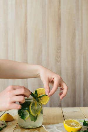 zijaanzicht van zelfgemaakte limonade koken met gele citroen, groene munt en water in glazen pot in houten interieur keuken Stockfoto