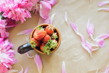 Top view of peonies and strawberries lie on a table on kraft paper photo in natural light Stock Photo